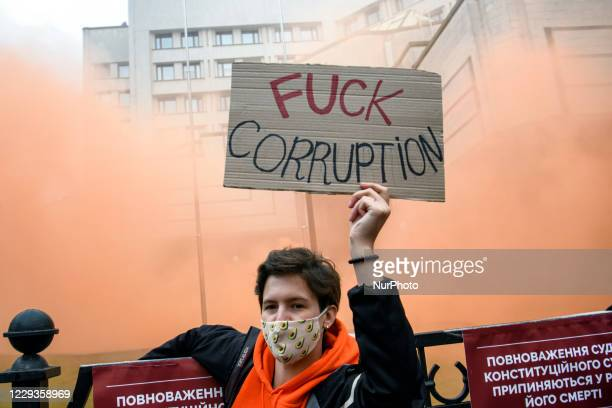 Protester stand among smoke during a rally outside the Constitutional Court building, after a court decision on anti-corruption laws in Kyiv, Ukraine...
