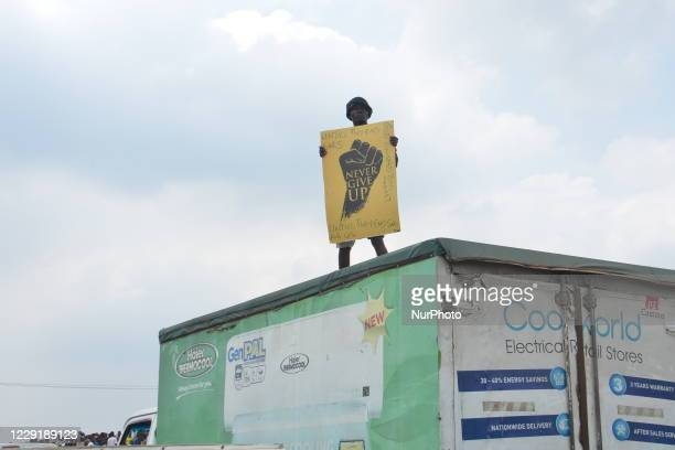 Protester standing on a truck gesture while holding a placard at Magboro, Ogun State, during a peaceful demonstration against police brutality in...