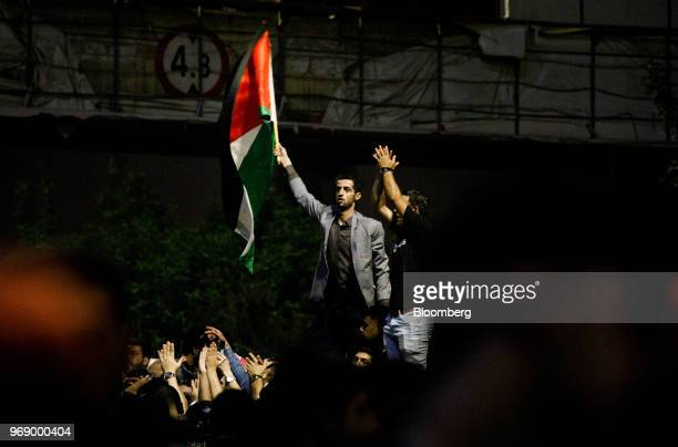 A protester stands above the crowd and waves a Jordanian flag during a demonstration against a draft income tax law near the prime minister's office...