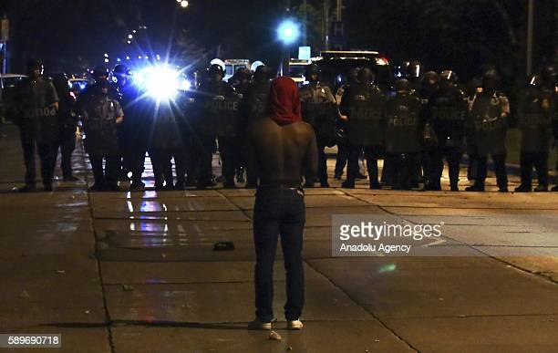 Protester stands against police officers during a protest held for Sylville Smith, who was shot and killed by a police officer as he reportedly...