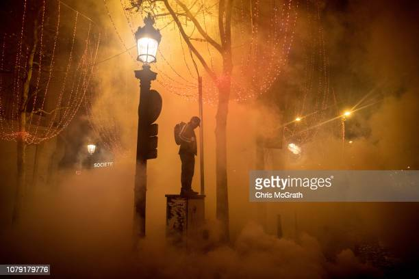 A protester stands amid clouds of tear gas during the 'yellow vests' demonstration on the ChampsElysées near the Arc de Triomphe on December 8 2018...