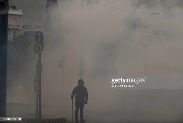 A protester stands amid tear gas during a demonstration against the agreement with Skopje to rename neighbouring country Macedonia as the Republic of...