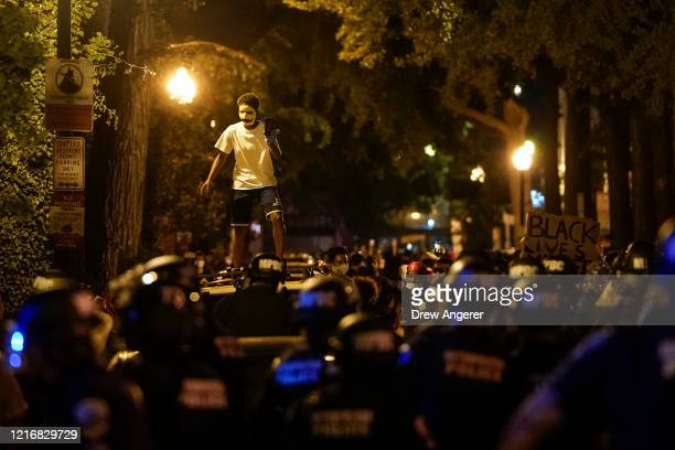 A protester stands atop a vehicle as he is surrounded by law enforcement during a protest on June 1 2020 in downtown Washington DC Protests and riots...