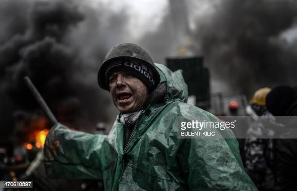 A protester stands behind barricades during clashes with police on February 20 2014 in Kiev Ukraine's embattled leader announced a truce with the...
