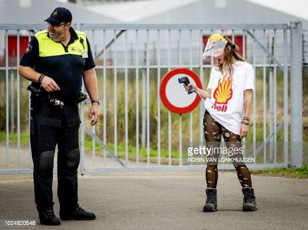 A protester stands beside an official during a demonstration against gas extraction from a gasfield in Groningen at Farmsum on August 28 2018 /...