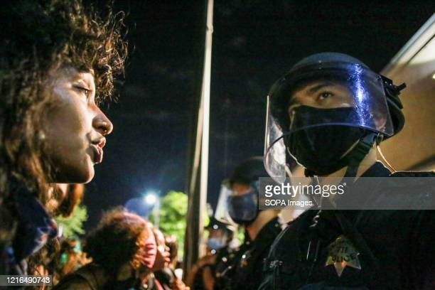 Protester stands face to face with a police officer during the demonstration. A peaceful protest, spurred by the death of George Floyd, turned...
