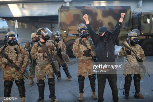 A protester stands in front of a line of National Guardsmen during a protest sparked by the death of George Floyd while he was in police custody on...