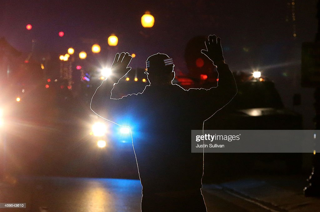 A protester stands in front of police vehicles with his hands up during a demonstration on November 24, 2014 in Ferguson, Missouri. A St. Louis County grand jury has decided to not indict Ferguson police Officer Darren Wilson in the shooting of Michael Brown that sparked riots in Ferguson, Missouri in August.