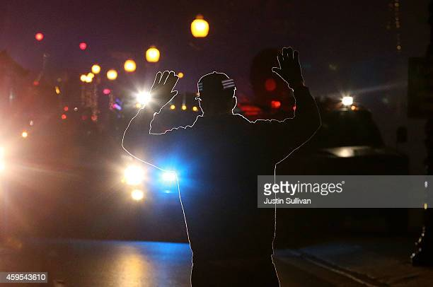 A protester stands in front of police vehicles with his hands up during a demonstration on November 24 2014 in Ferguson Missouri A St Louis County...