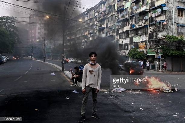 Protester stands near a burning makeshift barricade during a protest against the military coup, in Yangon on March 30, 2021.