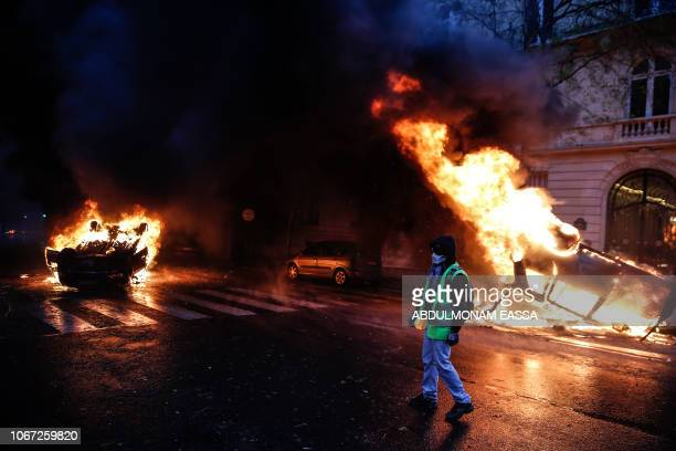 A protester stands near burning cars during a protest of Yellow vests against rising oil prices and living costs on December 1 2018 in Paris