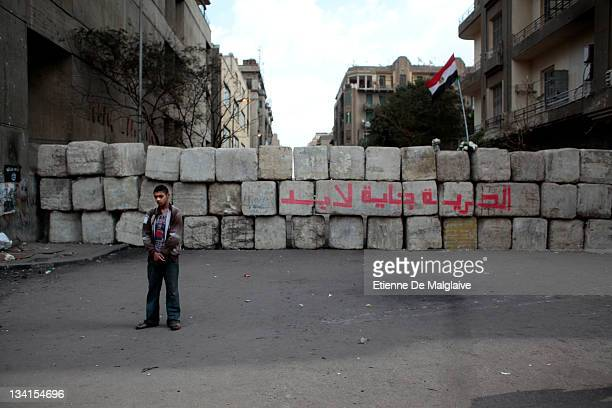 A protester stands next to a barricade mounted by the army to keep police from clashing with protestors in Mohammed Mahmoud near Tahrir Square on...