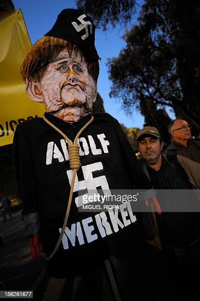 A protester stands next to a figure of German Chancellor Angela Merkel wearing a hat with a Nazi swastika symbol during protest against the visit of...
