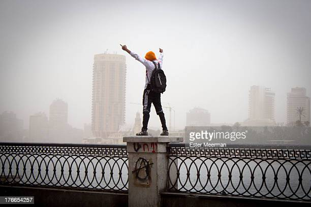 CONTENT] A protester stands on a fence on the banks of the Nile whilst fighting riot police in downtown Cairo
