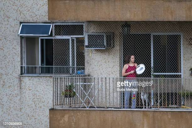 Protester stands on her balcony making noise with pots and pans against Brazil president Jair Bolsonaro during his press conference due to...