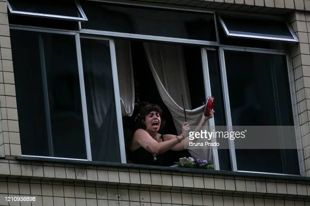 Protester stands on her window making noise with pots and pans against Brazil president Jair Bolsonaro during his press conference due to resignation...