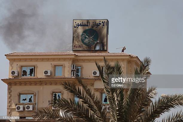 Protester stands on the roof of the headquarters of Egypt's Muslim Brotherhood as the building is ransacked in the suburb of Muqattam on July 1, 2013...