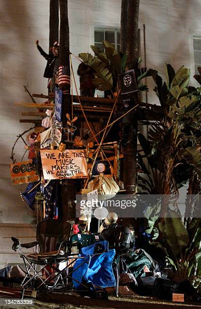A protester stands on top of a structure at the Occupy LA encampment as police dismantle the camp outside City Hall in Los Angeles November 30 2011...