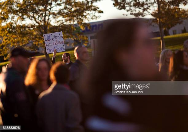 A protester stands outside Republican presidential nominee Donald Trump's campaign rally on October 10 2016 in WilkesBarre Pennsylvania Trump...