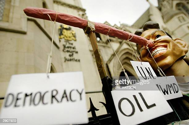 A protester stands outside the Royal Courts of Justice in London 28 January 2004 wearing a mask of British Prime Minister Toiny Blair Judge Lord...