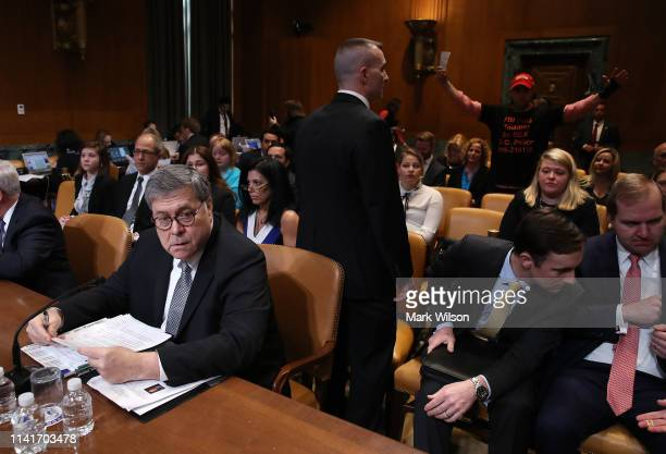 A protester stands up as US Attorney General William Barr testifies before the Senate Appropriations Committee in the Dirksen Senate Office Building...