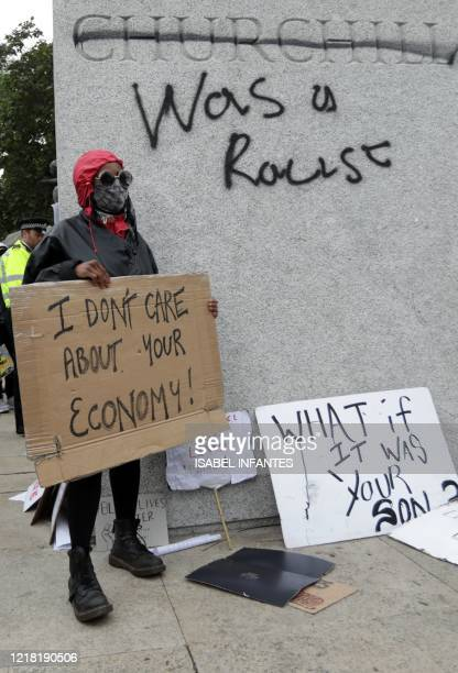 """Protester stands with a placard in front of the defaced statue of former British prime minister Winston Churchill, with the words """"was a racist""""..."""