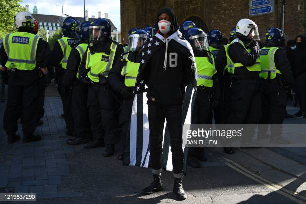 A protester stands with police officers near Waterloo Station after protesters supporting the Black Lives Matter movement clash with opponents in...