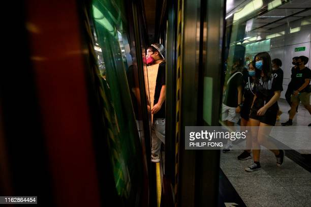 A protester steps on a train as he holds a placard during a protest in Tuen Mun district in Hong Kong on August 20 2019 Hong Kong's embattled leader...
