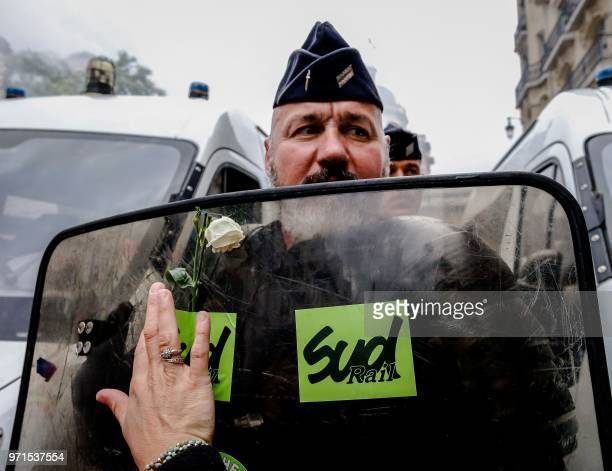 A protester sticks a rose with a SUD union sticker on the shield of a riot policeman during a demonstration of French railways workers over planned...