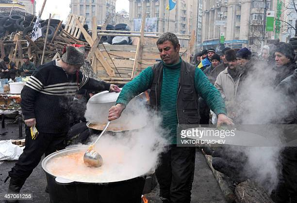 A protester stirs food on Independence Square in Kiev on December 16 2013 as Ukraine's opposition geared up to hold its second mass rally in days to...