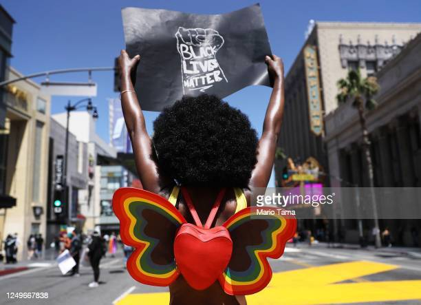 Protester strikes a pose while holding a 'Black Lives Matter' sign on Hollywood Boulevard during the All Black Lives Matter solidarity march,...