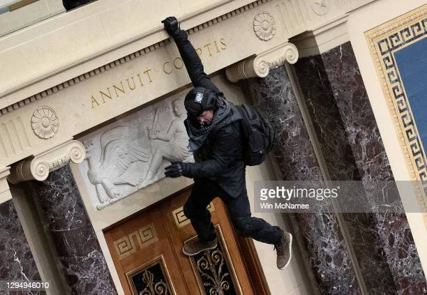 Protester supporting U.S. President Donald Trump jumps from the public gallery to the floor of the Senate chamber at the U.S. Capitol Building on...
