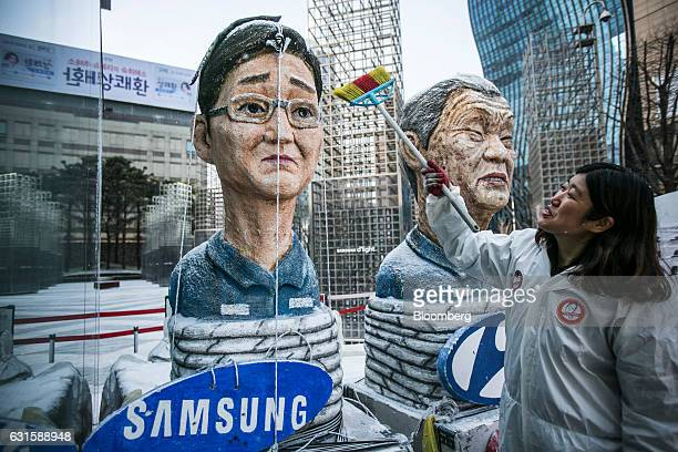 A protester sweeps effigies of Jay Y Lee covice chairman of Samsung Electronics Co left and Chung Mongkoo chairman of Hyundai Motor Co outside...