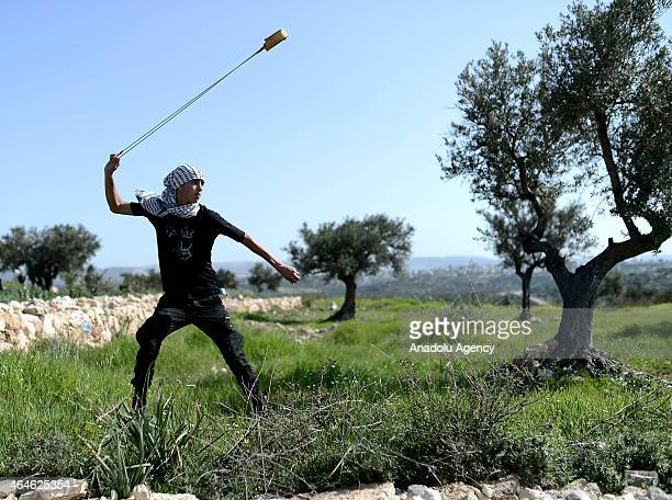 A protester swings a sling during a protest against the construction of Jewish settlement housing and the separation wall in the village of Belain in...