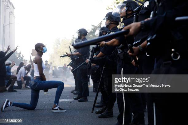 Protester takes a knee in front of San Jose Police officers during a protest on East Santa Clara Street in San Jose, Calif., on May 29 after the...