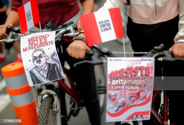 """Protester takes a sign on her bicycle reading """"Merino is Not My President"""" during a peaceful demonstration against the new government of interim..."""