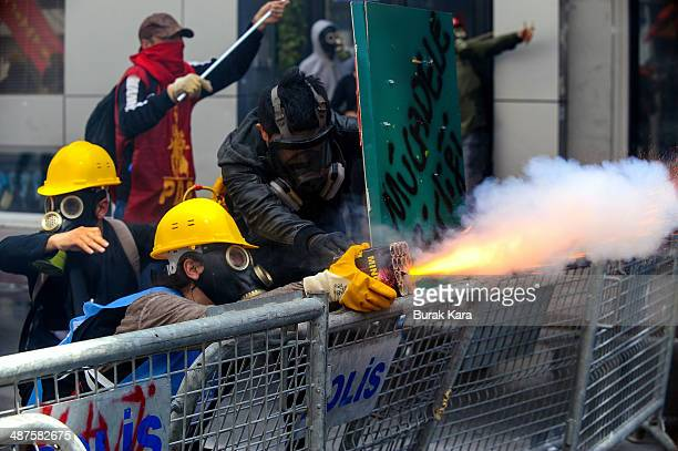 A protester takes aim at riot police with a flare gun during a May Day demonstration on May 1 2014 in Istanbul Turkey Turkish police fired water...