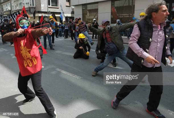 A protester takes aim at riot police with a slingshot during a May Day demonstration on May 1 2014 in Istanbul Turkey Turkish police fired water...