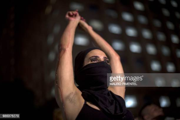 TOPSHOT A protester takes part in a demonstration against the murder of Brazilian councilwoman and activist Marielle Franco in front of Rio's...