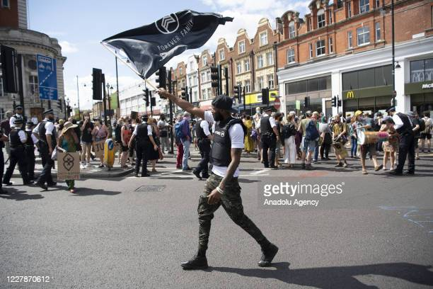 A protester takes part in supporting Reparations March UK Afrikan Emancipation Day  reclaim Brixton town centre in order to promote their demand of...