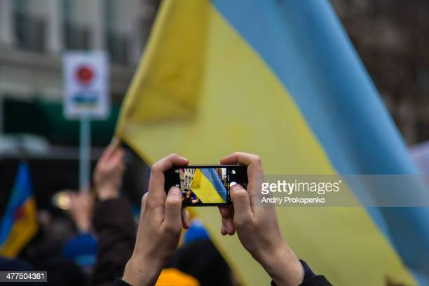 CONTENT] A protester taking picture with a smartphone of the Ukrainian national flag during a mass demonstration against Russian troops invading...