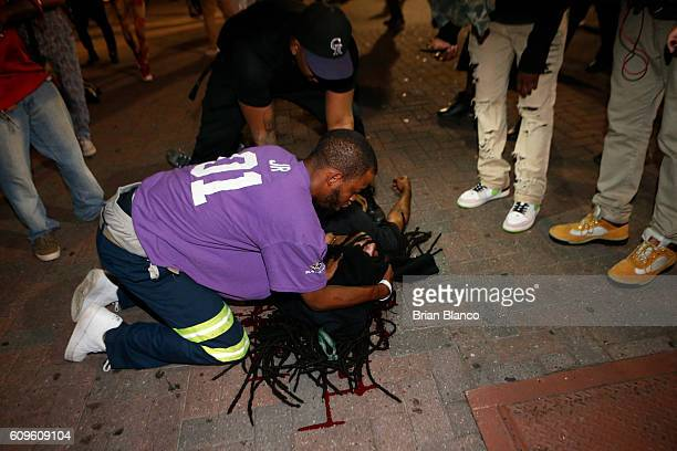 Protester tends to a seriously wounded man in the parking area of the the Omni Hotel during a march to protest the death of Keith Scott September 21,...