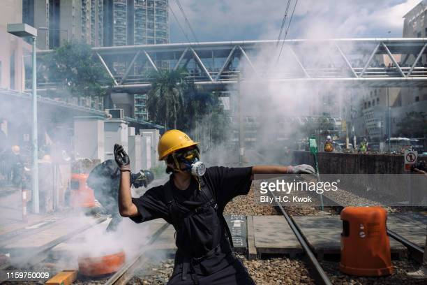 A protester throw a stone towards police outside Tin Shui Wai police station during a protest on August 05 2019 in Hong Kong China Prodemocracy...