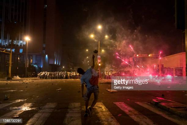 Protester throws a block of stone at the police during the confrontation as part of a protest against newly appointed interim president Manuel Merino...