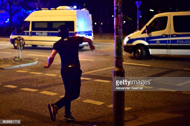 A protester throws a bottle towards police forces after erecting burning barricades in front of the Rote Flora leftwing centre during a march on July...