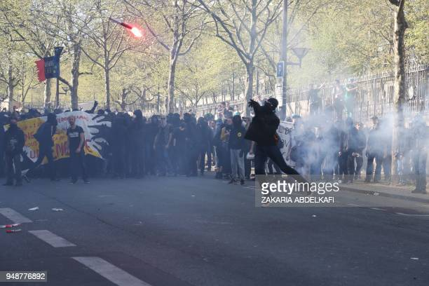 TOPSHOT A protester throws a burning flare during clashes with police at a demonstration on April 19 in Paris as part of a multi branch day of...