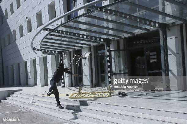 A protester throws a chair at Greek Ministry of National Education building as university students protest against some regulations at universities...