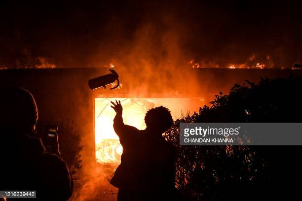 Protester throws a fire extinguisher in a burning building during a demonstration in Minneapolis, Minnesota, on May 29 over the death of George...