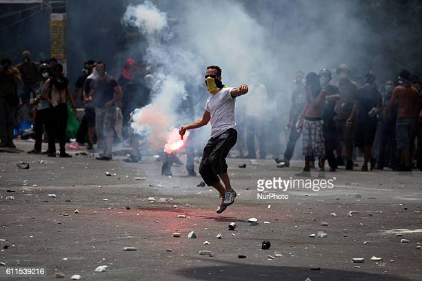 A protester throws a flare Demonstrations in Athens against austerity Another massive demonstration against the government 's plans for new austerity...