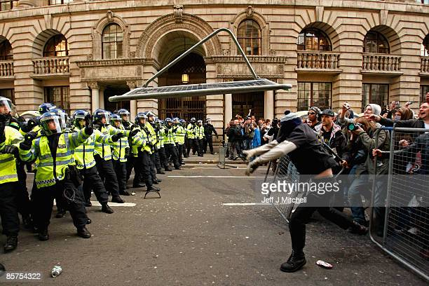 A protester throws a metal barricade at a police line as Anti capitalist and climate change activists demonstrate in the City of London on April 1...